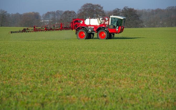 Ein Landwirt fährt mit einer Spritzmaschine über ein Feld.