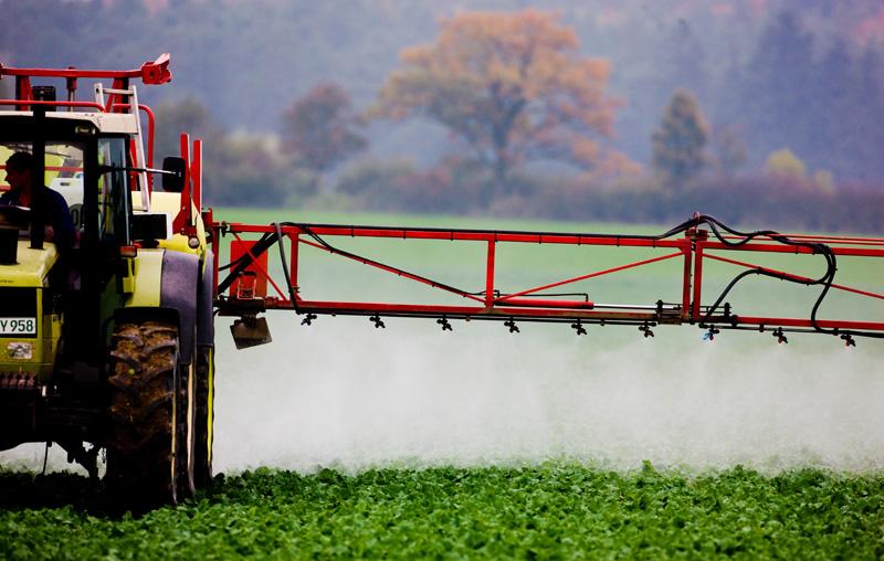 Tracktor versprüht Glyphosat auf Feld